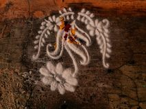 Rangoli of flower and plant in india ,pattern by decorative sand. Rangoli outside house by white decorative sand of flowering plant.Selective focus shot from Stock Photography