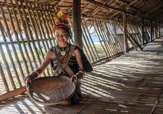 Rangus stam- kvinna i hennes traditionella stam- dräkt som arbetar i hennes hus i Kudat, Malaysia Arkivfoton