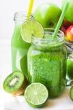 Ranja a caneca com o batido vegetal verde, garrafa com suco de fruto, quivi dispersado, cais, maçãs imagens de stock
