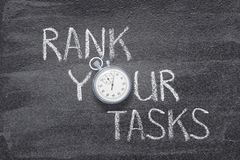 Rank your tasks watch. Rank your tasks phrase written on chalkboard with vintage precise stopwatch royalty free stock images