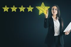Ranking and award concept. Attractive european woman drawing abstract star rating stock photography