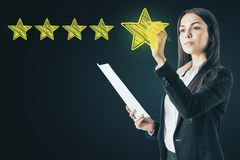 Ranking and exellence concept. Attractive european woman drawing abstract star rating stock photography