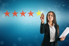 Ranking and feedback concept. Attractive young businesswoman on blue bokeh background with five star rating. Ranking and feedback concept royalty free stock photos