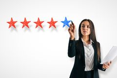 Ranking and feedback concept. Attractive young businesswoman on concrete background with five star rating. Ranking and feedback concept royalty free stock image
