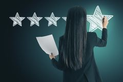 Ranking and leader concept. Attractive european woman drawing abstract star rating stock photography
