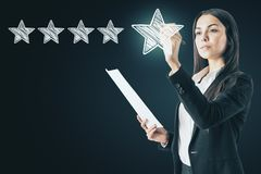 Ranking and service concept. Attractive european woman drawing abstract star rating stock image
