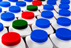 Ranks of capacities with covers various colors with dairy and sour-milk products Royalty Free Stock Photo