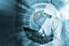 Concept of hacker attack with the hooded man with laptop in data center among supercomputers royalty free stock photo