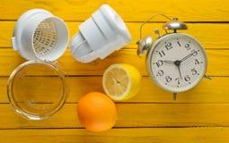 Ranku świeży sok od cytryny i pomarańcze Handmade juicer, budzik, cytrus owoc na żółtym drewnianym tle Odgórny widok Fotografia Royalty Free