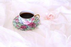 Ranku gorący coffe w kubku i małe menchie kwitniemy na białym atłasowym tle Zbliżenie, odgórny widok Sezonowy, ranek kawa fotografia royalty free