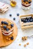Ranku granola z jogurtem, miodem i jagodami na bielu stole, zdjęcia stock