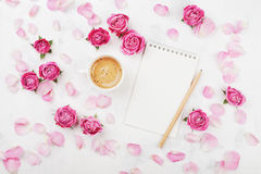 Ranku kawowy kubek dla śniadania, pusty notatnik, płatek i menchii róży kwiaty na białym stołowym odgórnym widoku w mieszkaniu, k Zdjęcie Stock