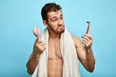 Ranku mężczyzna ma smutnego nieradego wyrażenie, wybiera żyletkę golić fotografia stock