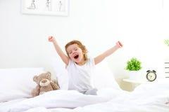 Ranku obudzenia dziecka dziewczyna w łóżku zdjęcia royalty free