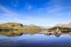 Rannoch moor loch highlands of scotland. Mountains and blue sky reflecting in the water of loch on rannoch moor in the highlands of scotland royalty free stock photo