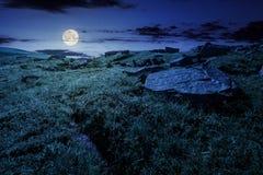 Rannuvoli il pendio di collina erboso con le rocce alla notte immagine stock