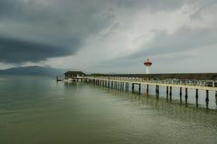 Ranong pier light house and cumulonimbus Stock Photo