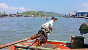 RANONG, THAILAND - 11 FEB 2014: local small boy manage with motor on wooden boat stock video footage