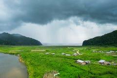 Rantee-Flussberg, der mit dem Dorf kultiviert regnet Lizenzfreie Stockfotografie