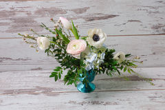 Ranunculus and the anemones in vase. Bouquet of ranunculus, anemones and other fresh flowers in blue vase stands on the background of vintage floor Stock Photography