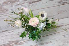 Ranunculus and the anemones in vase. Bouquet of ranunculus, anemones and other fresh flowers in blue vase stands on the background of vintage floor Royalty Free Stock Photos