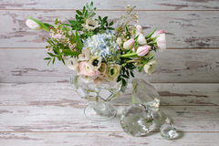 Ranunculus and the anemones in vase of glass. Bouquet of buttercups or ranunculus, anemones and other flowers in a vase of glass stands on the background of Stock Image