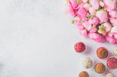 Ranunculus bouquet and homemade balls. Ranunculus bouquet lying on a light table and homemade vegan balls with different flavors, copy space, horizontal image Royalty Free Stock Photography
