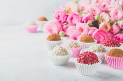 Ranunculus bouquet and homemade balls. Ranunculus bouquet lying on a light table and homemade vegan balls with different flavors, copy space, horizontal image Royalty Free Stock Image