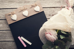 Ranunculus et tableau noir roses avec la craie Photographie stock