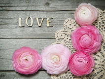 Ranunculus flowers and letters LOVE on wood Royalty Free Stock Photography