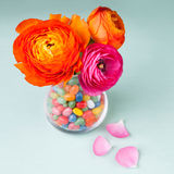 Ranunculus flowers with sweets Stock Photos
