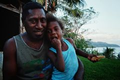 village school teacher Mr. Gibson with his cute daughter in front of their home on a hill above the ocean shore stock photography