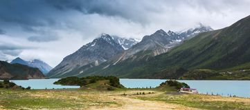 Ranwu Lake in the rainy season. The lakeside of Ranwu Lake is a large meadow of grassy grass, with blue lakes and snow-capped peaks, and the scenery is Stock Photo