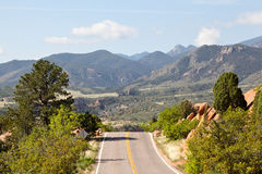 Raod and mountains for background. Road in national park Garden of the Gods Stock Photos