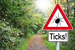 Raod sign in the forest with the german word for beware of ticks - Achtung Zecken royalty free stock images