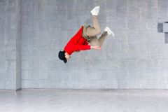 Rap dancer jumping on grey background. Portrait of a young male hip hop dancer jumping against grey background. Young rapper in high jump Stock Photography