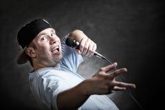 Rap singer man with microphone cool hand gesture. Rapper attitude rap singer hip Hop Dancer performing. Young man with microphone singing hand cool gesture black Royalty Free Stock Photo