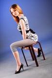 A rapariga adorável bonita senta-se na cadeira Fotografia de Stock