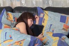 Rapariga adormecida com um portátil da tabuleta Imagens de Stock