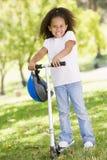 Rapariga ao ar livre ao sorrir do 'trotinette' foto de stock