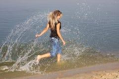 A rapariga apressa-se na água Imagens de Stock