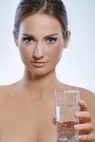 Rapariga bonita com água mineral no gla fotos de stock royalty free