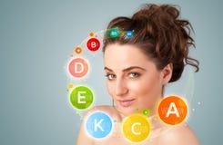 Rapariga bonita com ícones e símbolos coloridos da vitamina Foto de Stock Royalty Free