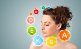 Rapariga bonita com ícones e símbolos coloridos da vitamina Fotografia de Stock Royalty Free