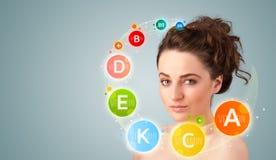 Rapariga bonita com ícones e símbolos coloridos da vitamina Imagens de Stock Royalty Free