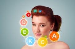 Rapariga bonita com ícones e símbolos coloridos da vitamina Foto de Stock