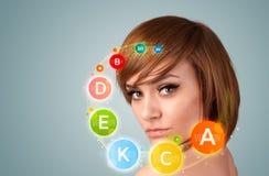 Rapariga bonita com ícones e símbolos coloridos da vitamina Imagens de Stock