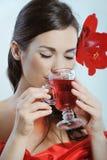 A rapariga bonita com a flor vermelha na audição bebe o chá do fruto fotos de stock