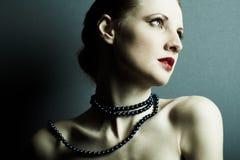 A rapariga bonita com uma obscuridade - grânulos azuis Fotografia de Stock