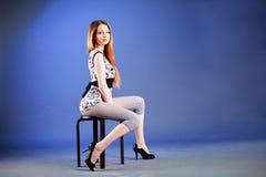 Rapariga bonita de fascínio na cadeira Fotos de Stock Royalty Free